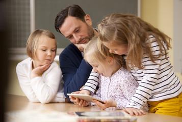 Teacher with schoolgirls using digital tablet in classroom