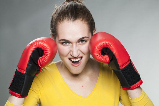 beautiful fighting young woman with boxing gloves happy to protect herself
