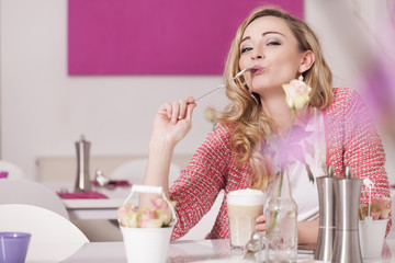 Blond woman sitting in a coffee shop with Latte Macciato