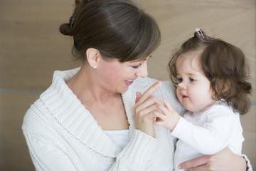 Woman applying creme on daughter's nose