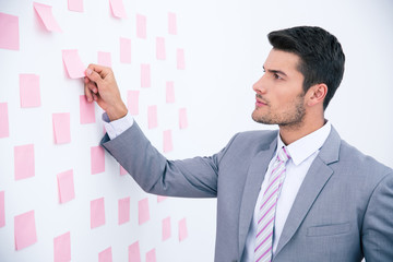 Businessman looking on sticker at wall
