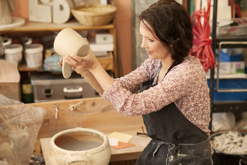 Potter in workshop working on earthenware pot