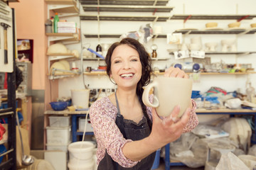 Portrait of smiling potter in studio holding jug