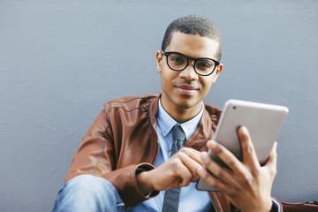Portrait of smiling businessman sitting outside using tablet