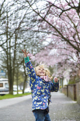 Little girl throwing cherry blossoms in the air