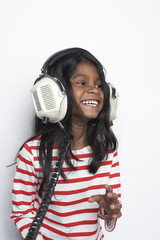 Portrait of smiling girl hearing music with headphones