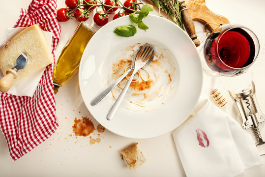 Spaghetti Bolognese, empty plate napkin with kissing lips