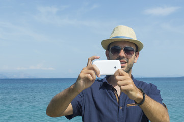 Man taking photos with his cell phone at the beach