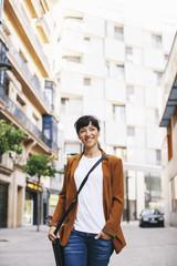 Spain, Barcelona, smiling businesswoman walking on a street