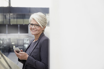 Portrait of smiling businesswoman with smartphone
