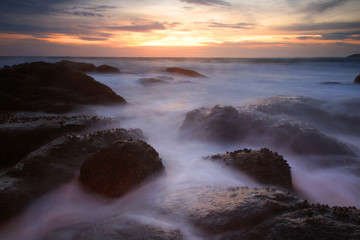 Seascape with motion water hitting rocks