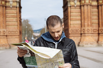 Spain, Barcelona, man looking at city map in front of trymphal arch