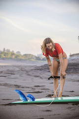 Indonesia, Bali, woman on the beach preparing for surfing