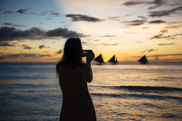 Woman photographing sailboats at sunset, Philippines