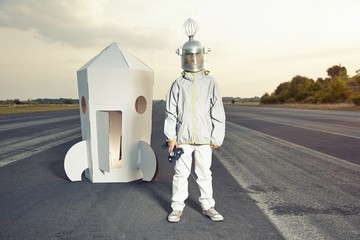 Boy dressed up as spaceman standing at cardboard rocket