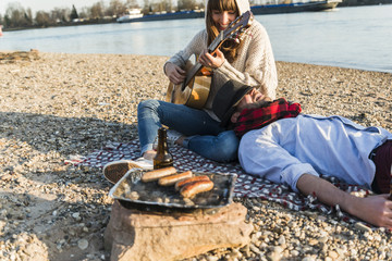 Couple sitting by the riverside, playing guitar