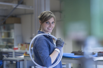 Technician in workshop carrying hose