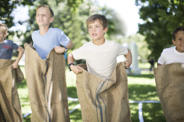 Boys competing in a sack race