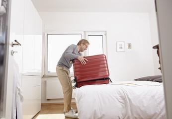 Senior man packing suitcase in bedroom