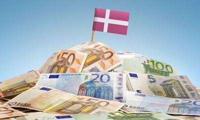 Flag of Denmark sticking in a pile of various european banknotes