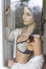 Sensual young woman in lingerie behind windowpane