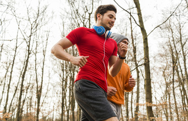 Two young men jogging in forest