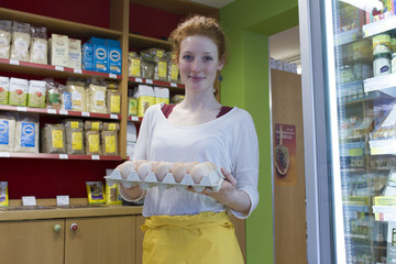 Portrait of smiling young woman in wholefood shop holding palette with fresh eggs