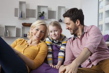 Portrait of happy mother, father and daughter at home