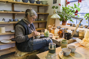 Potter in workshop painting a bowl