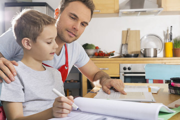 Father assisting his son by doing homework