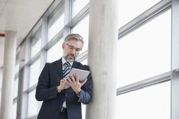 Businessman leaning against column using digital tablet