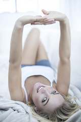 Portrait of blond woman lying on a couch stretching arms