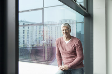 Portrait of smiling man with grey hair in front of a window