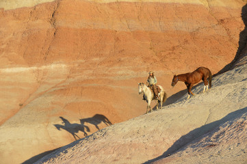 USA, Wyoming, cowgirl with two horses in badlands