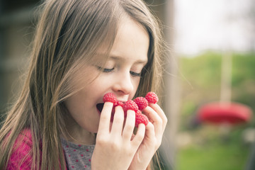 Girl eating raspberries from her fingers