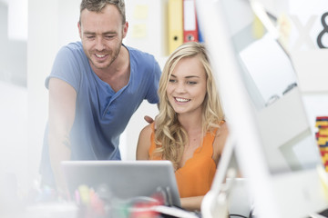 Creative office man looking at his colleague's laptop