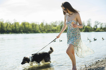 Germany, Mannheim, young woman walking with dog at River Rhine
