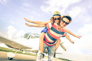 Happy hipster couple in love on airplane travel honeymoon