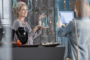 Woman showing bead necklace to a customer taking pictures with a tablet