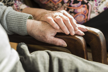 Hands of senior couple on arm rest