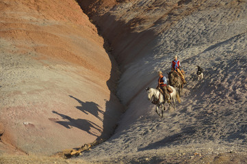 USA, Wyoming, cowgirl and cowboy riding in badlands