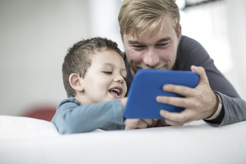 Father and little son on couch looking at a tablet
