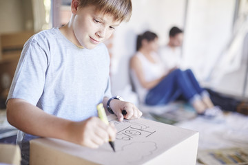 Family moving house, boy writing on a box