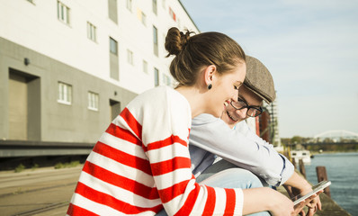 Smiling young man and woman looking at digital tablet