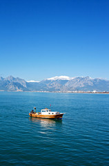 Small fishing boat with snow covered mountains in Antalya Turkey