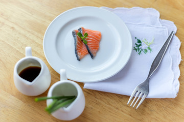 salmon in white dish and fork on wooden