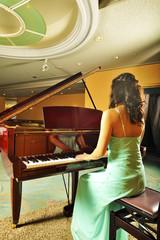 室内でグランドピアノを弾く女性の後ろ姿