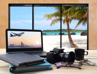 working table and window seat over looking the sea and beach with perspective view of jet airliner in flight from screen computer
