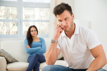 Defocused Woman In Front Of Sad Young Man