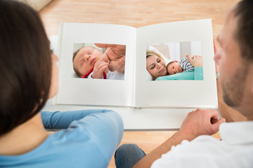 Couple Looking At Baby's Photo Album